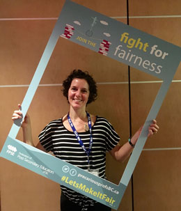 professor holding sign that reads 'fight for fairness'