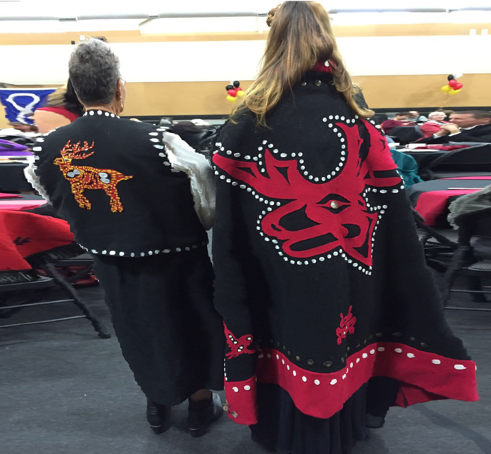 backs of two women wearing First Nations clothing