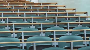 Rows of empty desks in a lecture hall